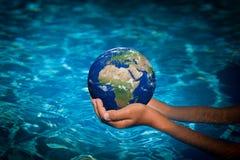 Enfant tenant la planète de la terre dans des mains Images libres de droits