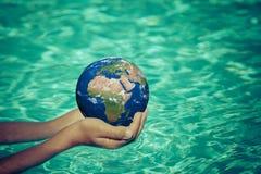 Enfant tenant la planète de la terre dans des mains Photos libres de droits