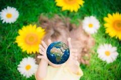 Enfant tenant la planète de la terre dans des mains Photographie stock