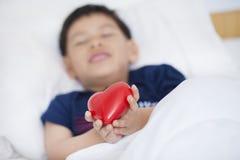 Enfant tenant le coeur rouge dans des ses mains, amour de offre sur le bedro Photographie stock