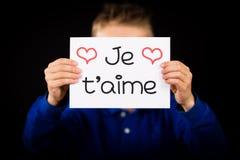 Enfant tenant le signe avec l'aime français de Je T de mot - je t'aime Images stock