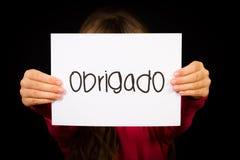 Enfant tenant le signe avec le mot portugais Obrigado - merci Image libre de droits