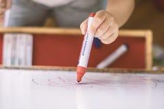 Enfant tenant un crayon en plan rapproché de tableau blanc Photographie stock
