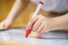 Enfant tenant un crayon en plan rapproché de tableau blanc Photos stock