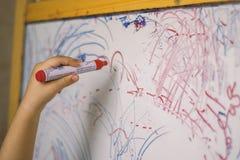 Enfant tenant un crayon en plan rapproché de tableau blanc Photographie stock libre de droits