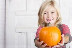Enfant tenant un petit potiron Photographie stock