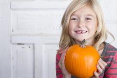 Enfant tenant un petit potiron Image libre de droits