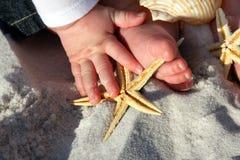 Enfant tenant une étoile de mer à la plage Image stock