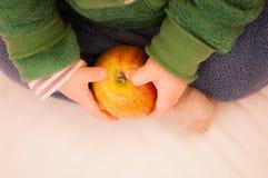 Enfant tenant une pomme dans une main Photos stock