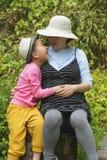 Enfant touchant l'abdomen enceinte de mamans Photographie stock