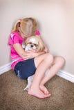 Enfant triste et chien se reposant dans le coin photos stock