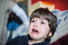 Enfant triste et pleurant dans sa maison Photo stock