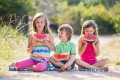 Enfant trois de sourire heureux mangeant la pastèque Image stock