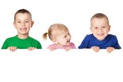 Enfant trois derrière le panneau blanc Photos stock