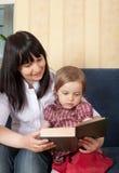 Enfantez afficher un livre avec son petit descendant Photographie stock