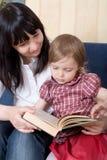 Enfantez afficher un livre avec son petit descendant Photos stock