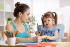Enfantez aider son enfant à couper le papier coloré photos stock