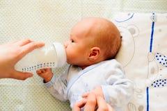 Enfantez alimenter son bébé avec une bouteille à lait image libre de droits
