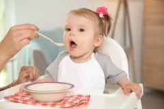 Enfantez alimenter son petit bébé mignon avec la maison saine de nourriture image libre de droits
