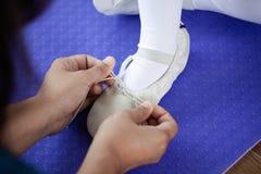 Enfantez attacher des chaussures de pointe de pieds à sa fille photos stock