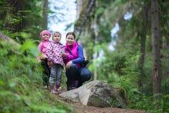 Enfantez avec deux petites filles de jumeaux marchant dans la forêt Photos stock