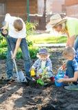 Enfantez avec trois fils d'enfants plantant un arbre et l'arrosant ensemble dans le jardin Photographie stock