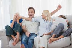 Enfantez cacher le visage de son fils tout en observant un film d'horreur photos stock