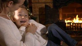 Enfantez chatouiller sa petite fille mignonne tandis qu'elle s'asseyant sur des mains du ` s de mère banque de vidéos
