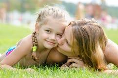 Enfantez embrasser sa fille se trouvant sur la pelouse d'herbe verte photographie stock