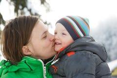 Enfantez embrasser son fils dans un paysage neigeux d'hiver Photo libre de droits