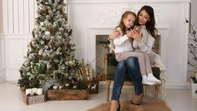 Enfantez en montrant à sa petite fille comment introduire un message à Santa au téléphone photo libre de droits