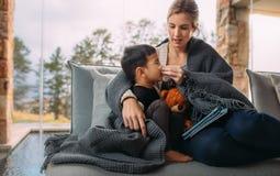 Enfantez essuyer le nez de son fils malade à la maison photos libres de droits
