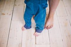 Enfantez et des jambes d'un fils sur le plancher en bois photo libre de droits