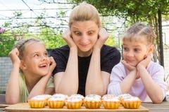 Enfantez et deux filles ayant l'amusement et regardant des petits gâteaux de Pâques Image stock