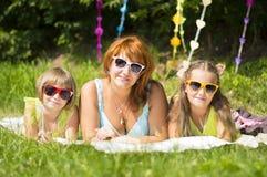 Enfantez et deux filles se trouvant sur l'herbe Images stock