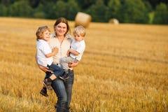 Enfantez et deux petits garçons de jumeaux sur le gisement de foin Images libres de droits