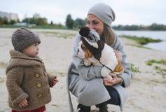 Enfantez et le petit jeu de fille avec un chiot dans le chapeau sur la banque de la rivière d'automne Images libres de droits