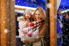 Enfantez et peu de fille d'enfant mangeant la pomme crystalized sur Noël Photo libre de droits