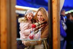 Enfantez et peu de fille d'enfant mangeant la pomme crystalized sur Noël Photos libres de droits