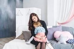 Enfantez et sa fille avec du charme de bébé dans la chambre à coucher Amour maternel Photos stock
