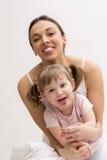 Enfantez et sa fille ayant l'amusement et montrant la langue Image stock