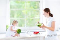 Enfantez et sa fille d'enfant en bas âge faisant cuire la salade saine image libre de droits