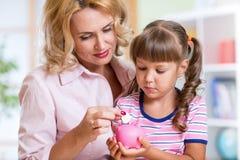 Enfantez et sa fille mettant des pièces de monnaie dans porcin Images libres de droits