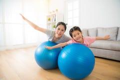 Enfantez et sa fille se trouvant sur la boule photos libres de droits