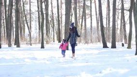 Enfantez et sa petite fille marchant en bois neigeux banque de vidéos