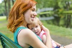 Enfantez et sa petite fille s'asseyant sur un banc de parc Photographie stock