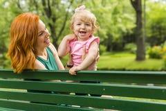 Enfantez et sa petite fille s'asseyant sur un banc de parc Images libres de droits