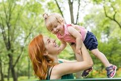 Enfantez et sa petite fille s'asseyant sur un banc de parc Photos libres de droits