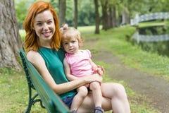 Enfantez et sa petite fille s'asseyant sur un banc de parc Image stock