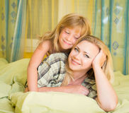 Enfantez et sa petite fille se situant dans le lit et le sourire famille Temps de lit Image stock